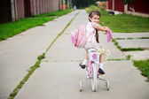 Young school girl with pink backpack on a bicycle — Stock Photo