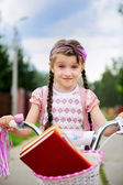 Young school girl rides her pink bicycle — Stock Photo