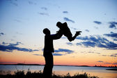 Silhouette of father and daughter in the sunset — Stock Photo