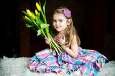 Portrait of adorable sunny child girl with tulips — Stock Photo