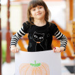 Young girl outdoors acts as a black cat on Halloween — Stock Photo