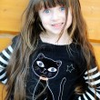 Stock Photo: Young girl outdoors acts as a black cat on Halloween