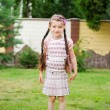 Stock Photo: Young school girl with pink backpack poses outdoors
