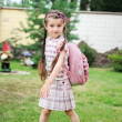 Foto Stock: Young school girl with pink backpack poses outdoors
