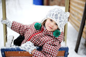 Adorable child girl enjoys seesaw in winter — Stock Photo