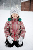Adorable smiling child girl has fun in the snow — Stock Photo