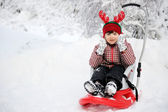 Adorable child girl in horned hat sled in snow — Stock Photo