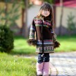 Cute child girl with long dark hair poses outdoors — Stock Photo #6616449