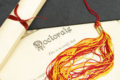 A closeup shot of a doctorate and diploma scroll with the tassels of a mortar board. — Stock Photo