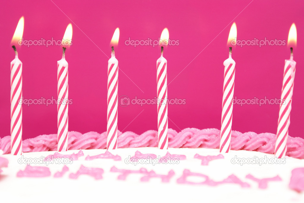Lit birthday candles on a pink cake are waiting to be blown out as a wish is being made. — Stock Photo #6717677