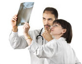 Two doctors watching an xray over a white background — Stockfoto