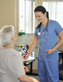 Young nurse with senior patient — Stock Photo
