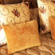 Beautiful cushions on bed — Stock Photo
