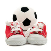 Red baby sneakers with a ball — Stock Photo