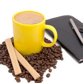 Yellow cup of coffee stands before deferred notebook — Stock Photo
