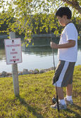 "Boy reading the ""No Fishing"" sign — Stock Photo"