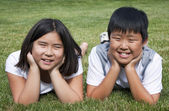 Brother and Sister Laying in the Grass — Stock Photo
