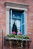 Window with flowers and brick wall — Stock Photo