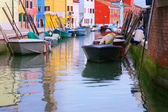 Colorful buildings and boat in Burano island sunny street — Stock Photo