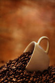 Coffee cup on roasted coffee beans — Stock Photo