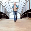 Young man running across a pedestrian bridge. - Stock Photo