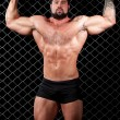 Royalty-Free Stock Photo: Bodybuilder posing in front of chain link.