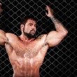 Bodybuilder posing in front of chain link. — Foto Stock