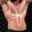 Bodybuilder posing in front of chain link. — Stock Photo