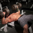 Male bodybuilder working out in a gym. — Stockfoto