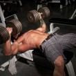 Male bodybuilder working out in a gym. - Stock Photo