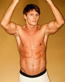 Muscular male bodybuilder in front of gold background. — Stock Photo