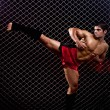 Mixed martial artist posed in front of chain link — Stock Photo