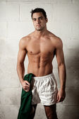 Male rugby player in front of concrete block wall. — Stock Photo