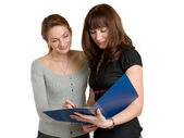 Two young women get acquainted oneself with the document. — Stock Photo