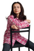 Woman sits on a chair back to front. — Stock Photo