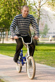 The adult man goes for a drive on a children's bicycle. — Stock Photo