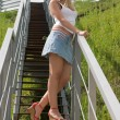 Pretty girl stands on a stairs. — Stock Photo