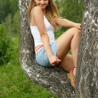 Pretty girl sit on birch in a park. — Stock Photo