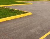 Parking lot yellow striping grass — Stock Photo