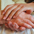 Two Generations embracing and Holding Hands - Grandmother Daughter - Stock Photo