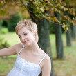 Portrait of young smiling woman posing near the tree - Stock Photo