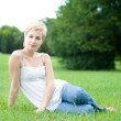 Beautiful attractive woman sitting on a green grass - Stock Photo