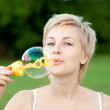Young woman start soap bubbles - Stock Photo