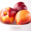 Three peaches on a plate - Stock Photo
