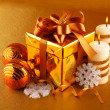 Christmas gift in gold box with bow - Stok fotoğraf