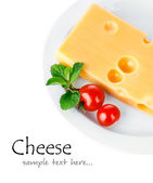 Yellow cheese in plate with tomatoes and leaf — Stock Photo