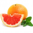 Fresh grapefruit fruit with cut and green leaves — Stock Photo