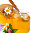 Sweet honey in glass jars with spoon and flowers - Stock Photo
