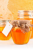 Sweet honey in glass jars — Stock Photo