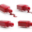 Set of red nail polish pouring from overturned bottle - Stock Photo